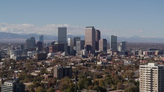 DX0001_001741 - 5.7K stock footage aerial video slow ascent by the city's skyline with mountains in background, Downtown Denver, Colorado
