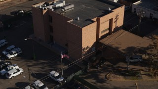 DX0001_001765 - 5.7K stock footage aerial video of a reverse view of a brick police station and flag in Denver, Colorado
