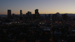 DX0001_001873 - 5.7K stock footage aerial video of passing and then approaching the city's skyline at twilight, Downtown Denver, Colorado