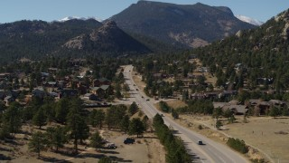 DX0001_001976 - 5.7K stock footage aerial video of descending past cars on a road through the town of Estes Park, Colorado