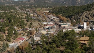 DX0001_001989 - 5.7K stock footage aerial video fly over trees to reveal shops on road through Estes Park, Colorado