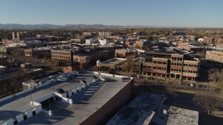 DX0001_002019 - 5.7K stock footage aerial video fly away from a row of brick office buildings and shops in Fort Collins, Colorado
