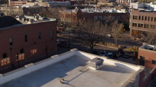 DX0001_002042 - 5.7K stock footage aerial video of passing brick office buildings and street level shop in Fort Collins, Colorado