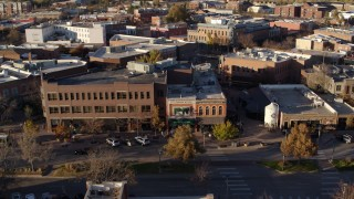 DX0001_002060 - 5.7K stock footage aerial video of people and cars passing a shop with green awning and brick office building in Fort Collins, Colorado