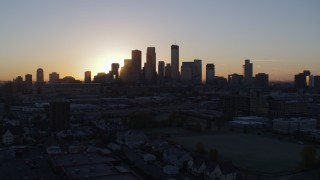 DX0001_002062 - 5.7K stock footage aerial video of a view of the rising sun behind the city's skyline in Downtown Minneapolis, Minnesota