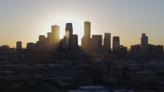 DX0001_002074 - 5.7K stock footage aerial video focus on city skyline at sunrise during slow flyby and descent in Downtown Minneapolis, Minnesota