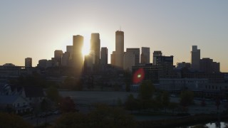 DX0001_002080 - 5.7K stock footage aerial video of the rising sun behind the city skyline seen during ascent in Downtown Minneapolis, Minnesota
