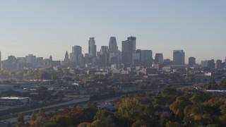 DX0001_002090 - 5.7K stock footage aerial video ascend from behind trees to reveal skyline at sunrise in Downtown Minneapolis, Minnesota