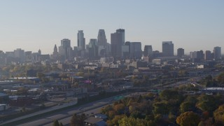 DX0001_002100 - 5.7K stock footage aerial video ascend from park to reveal the city's downtown skyline at sunrise in Downtown Minneapolis, Minnesota