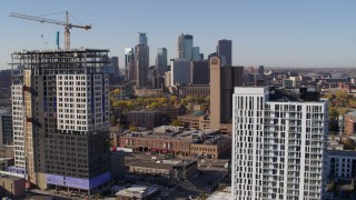 DX0001_002118 - 5.7K stock footage aerial video of flyby apartment building at sunrise with skyline in background in Downtown Minneapolis, Minnesota