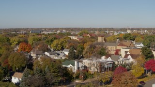 DX0001_002132 - 5.7K stock footage aerial video descend behind trees in suburban neighborhood at sunrise in Minneapolis, Minnesota