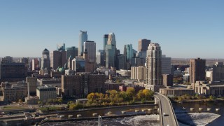 DX0001_002136 - 5.7K stock footage aerial video slowly flying by the skyline, seen from a bridge spanning the river in Downtown Minneapolis, Minnesota