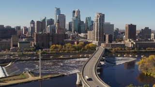 DX0001_002143 - 5.7K stock footage aerial video flying by a bridge spanning the river with a view of the skyline, Downtown Minneapolis, Minnesota