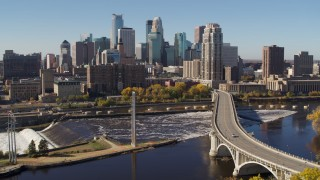 DX0001_002144 - 5.7K stock footage aerial video descending by a bridge spanning the river with a view of the skyline, Downtown Minneapolis, Minnesota