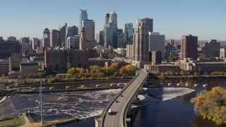 DX0001_002146 - 5.7K stock footage aerial video descend by a bridge spanning the river for stationary view of the skyline, Downtown Minneapolis, Minnesota