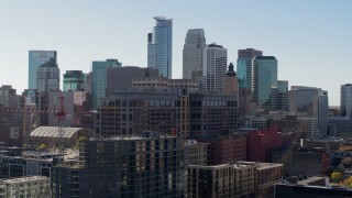 DX0001_002164 - 5.7K stock footage aerial video descend by office building and construction, city's skyline in background, Downtown Minneapolis, Minnesota