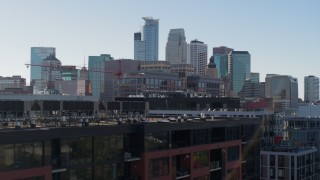 DX0001_002165 - 5.7K stock footage aerial video descend by office building and city's skyline, reveal apartment building, Downtown Minneapolis, Minnesota