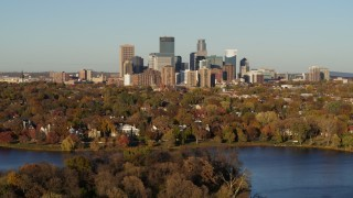 DX0001_002208 - 5.7K stock footage aerial video flyby the skyline of Downtown Minneapolis, Minnesota before descending toward lake