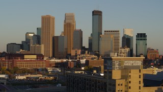 DX0001_002223 - 5.7K stock footage aerial video ascend while flying by the city's downtown skyline at sunset in Downtown Minneapolis, Minnesota
