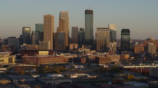 DX0001_002226 - 5.7K stock footage aerial video of slowly flying away from the city's downtown skyline at sunset in Downtown Minneapolis, Minnesota