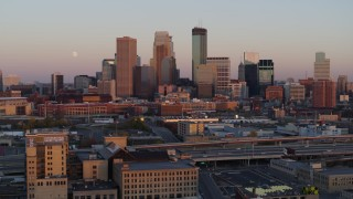 DX0001_002237 - 5.7K stock footage aerial video reverse view of the city's skyline at sunset with moon in the sky, Downtown Minneapolis, Minnesota