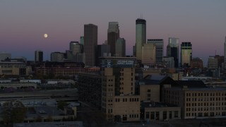 DX0001_002251 - 5.7K stock footage aerial video flying by the city's downtown skyline at twilight, reveal moon and market, Downtown Minneapolis, Minnesota