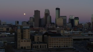DX0001_002252 - 5.7K stock footage aerial video passing by the city's downtown skyline at twilight, reveal moon and market, Downtown Minneapolis, Minnesota