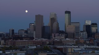 DX0001_002259 - 5.7K stock footage aerial video ascend with view of moon near the city's downtown skyline at twilight, Downtown Minneapolis, Minnesota