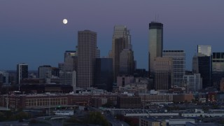 DX0001_002260 - 5.7K stock footage aerial video of moon above the city's downtown skyline at twilight, Downtown Minneapolis, Minnesota