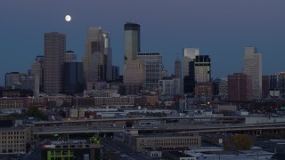 DX0001_002265 - 5.7K stock footage aerial video flyby the city's skyline with the moon in the sky at twilight, Downtown Minneapolis, Minnesota