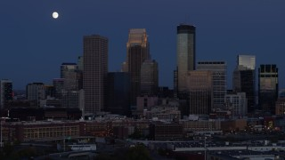 DX0001_002272 - 5.7K stock footage aerial video of skyscrapers in city skyline and the moon in the sky at twilight, Downtown Minneapolis, Minnesota