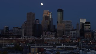 DX0001_002273 - 5.7K stock footage aerial video of the moon above skyscrapers in city skyline at twilight, Downtown Minneapolis, Minnesota