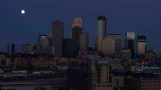 DX0001_002274 - 5.7K stock footage aerial video flyby the moon above skyscrapers in city skyline at twilight, Downtown Minneapolis, Minnesota