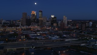 DX0001_002279 - 5.7K stock footage aerial video of a view of the moon above city's downtown skyline at twilight, Downtown Minneapolis, Minnesota