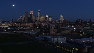 DX0001_002282 - 5.7K stock footage aerial video flying by market building with the moon above city's downtown skyline at twilight, Downtown Minneapolis, Minnesota