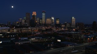 DX0001_002284 - 5.7K stock footage aerial video descend with view of moon above city's skyline at twilight, Downtown Minneapolis, Minnesota