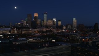 DX0001_002285 - 5.7K stock footage aerial video ascend with view of moon above city's skyline at twilight, Downtown Minneapolis, Minnesota