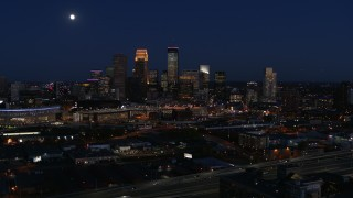 DX0001_002288 - 5.7K stock footage aerial video of a reverse view of the moon above city's skyline at twilight, Downtown Minneapolis, Minnesota