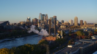 DX0001_002289 - 5.7K stock footage aerial video ascend to reveal power plant, and the city skyline across the river at sunrise, Downtown Minneapolis, Minnesota