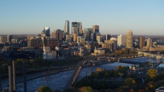 DX0001_002295 - 5.7K stock footage aerial video of flying by the city skyline across the Mississippi River at sunrise, Downtown Minneapolis, Minnesota