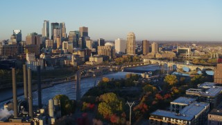 DX0001_002296 - 5.7K stock footage aerial video of flying by bridge and Mississippi River at sunrise, with view of skyline, Downtown Minneapolis, Minnesota