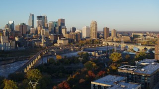DX0001_002297 - 5.7K stock footage aerial video flyby bridge and river at sunrise, reveal power plant, with view of skyline, Downtown Minneapolis, Minnesota