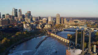 DX0001_002299 - 5.7K stock footage aerial video flying bridge and river with view of skyline at sunrise, Downtown Minneapolis, Minnesota
