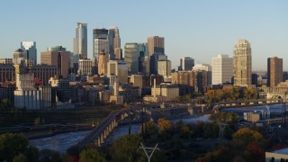 DX0001_002303 - 5.7K stock footage aerial video of a view of skyline across the Mississippi River at sunrise, Downtown Minneapolis, Minnesota
