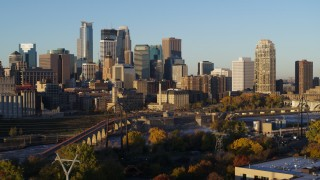 DX0001_002310 - 5.7K stock footage aerial video pass the city skyline across the river at sunrise, reveal smoke stacks, Downtown Minneapolis, Minnesota
