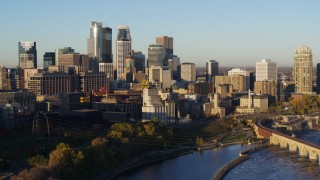 DX0001_002312 - 5.7K stock footage aerial video focus on city skyline while flying by the river at sunrise, Downtown Minneapolis, Minnesota
