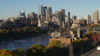 DX0001_002327 - 5.7K stock footage aerial video descend by riverfront power plant at sunrise, with skyline in background, Downtown Minneapolis, Minnesota