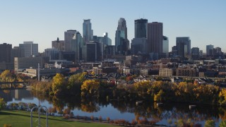DX0001_002334 - 5.7K stock footage aerial video descend by the river with view of city skyline, Downtown Minneapolis, Minnesota