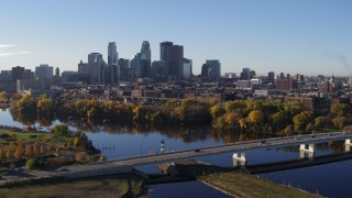 DX0001_002337 - 5.7K stock footage aerial video reverse view of city's skyline during ascent from bridge and river, Downtown Minneapolis, Minnesota