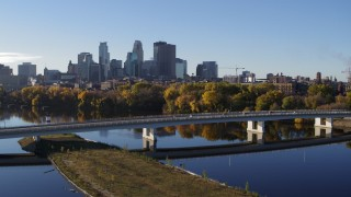DX0001_002339 - 5.7K stock footage aerial video approach and fly over bridge and river, focus on skyline of Downtown Minneapolis, Minnesota